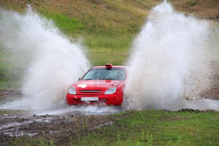 Red rally car and water splash