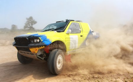Power yellow off-road car on dirt road