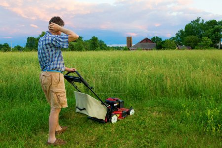 Photo for Man is tasked to mow a field of tall grass - Royalty Free Image