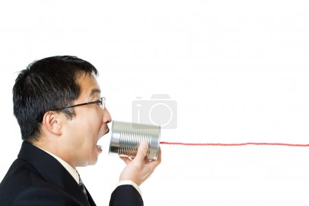 Photo for An isolated shot of a businessman communicating with a tin can phone - Royalty Free Image