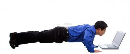 Photo for An isolated shot of a businessman doing push up while working on his laptop - Royalty Free Image