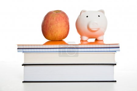 Photo for A shot of an apple and a piggy bank on top of books, can be used for education concept - Royalty Free Image