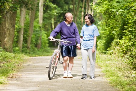 Photo for A couple senior asian talking while walking and exercising at a park - Royalty Free Image