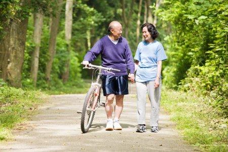 Photo pour Un couple asiatique senior parle tout en marchant et en faisant de l'exercice dans un parc - image libre de droit