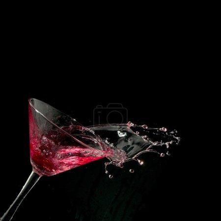 Photo pour Martini rouge cocktail éclaboussures en verre sur fond noir - image libre de droit