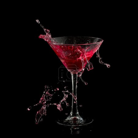Photo for Red martini cocktail splashing into glass on black background - Royalty Free Image