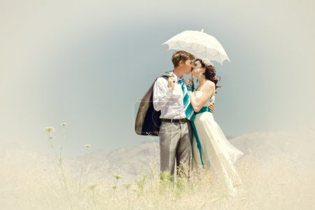 The groom and the bride kiss under summer the hot sun in mountai
