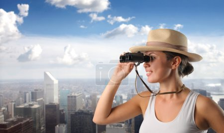 Photo for Smiling woman using binoculars with cityscape on the background - Royalty Free Image