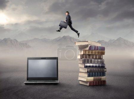 Photo pour Homme d'affaires sautant d'une pile de livres à un ordinateur portable - image libre de droit