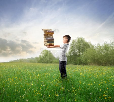 Photo for Child holding a stack of books on a green meadow - Royalty Free Image
