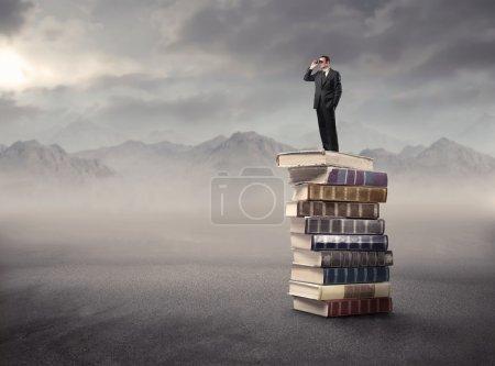 Photo pour Homme d'affaires debout sur une pile de livres et utilisant des jumelles - image libre de droit