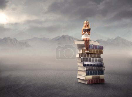 Photo for Young girl sitting on a stack of books and reading - Royalty Free Image