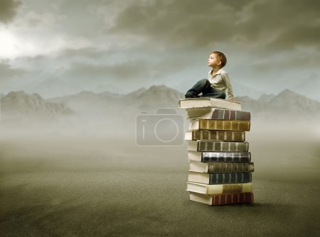 Photo for Child sitting on a stack of books in the mountains - Royalty Free Image