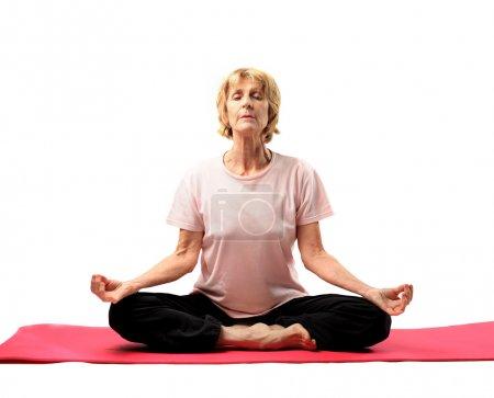 Photo pour Femme âgée faisant du yoga sur un tapis - image libre de droit