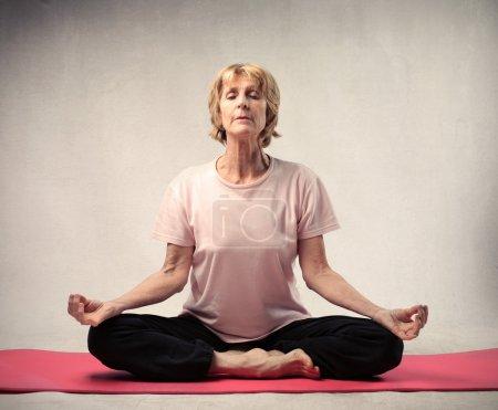 Photo pour Femme âgée faisant un exercice de yoga sur un tapis - image libre de droit