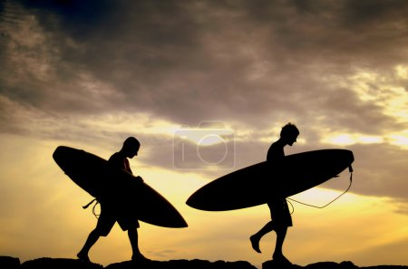 Two Surfers Carrying Their Boards Home At Sunset