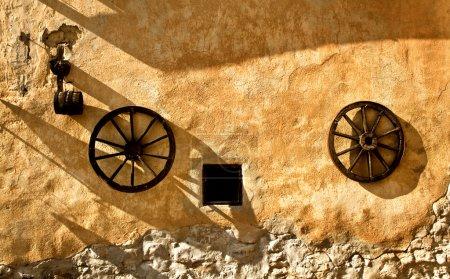 Photo pour Deux roues anciennes sur le vieux mur de la ville médiévale - image libre de droit
