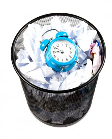 Photo for Blue alarm clock sat in a waster paper basket - Royalty Free Image