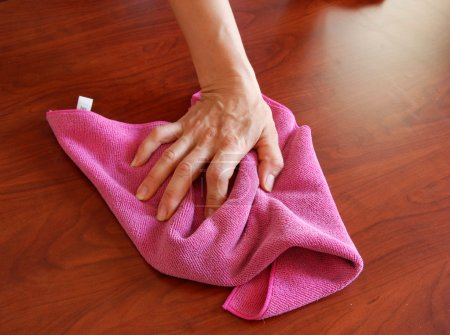 Hand wiping wooden surface with pink rag...