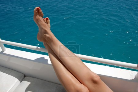 Photo for Woman crossed legs on yacht over blue sea - Royalty Free Image