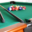 Billiards green table with balls and two black cue...