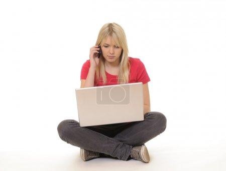 Photo pour Belle jeune femme avec ordinateur portable et téléphone mobile - image libre de droit