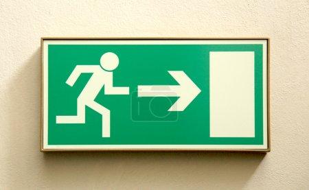 Emergency exit sign on a wall - closeup...