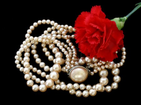 Vintage pearl necklace with red carnation.