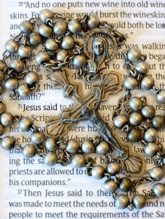 Vintage rosary beads on page of a bible.