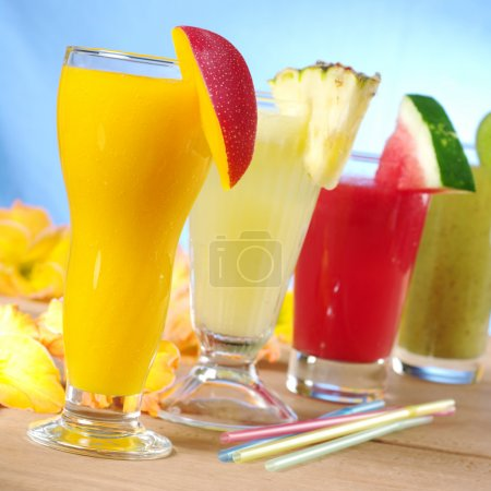 Photo for Mango, pineapple, watermelon and kiwi smoothie with drinking straws on wood (Selective Focus, Focus on the mango smoothie in the front) - Royalty Free Image