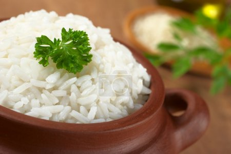 Photo for Cooked white rice garnished with parsley in a rustic bowl (Selective Focus, Focus on the parsley and the rice around) - Royalty Free Image