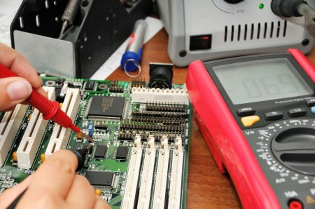 Photo for Technician with multimeter probes at his work place with soldering iron, multimeter and circuit board - Royalty Free Image