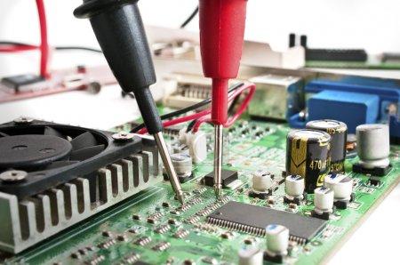 Photo pour Sondes multimètres examinant une carte de circuit informatique - image libre de droit