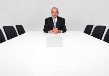 Photo for Businessman sitting alone in the empty boardroom - Royalty Free Image