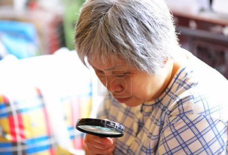Photo pour Femme âgée utilisant une loupe - image libre de droit