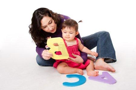 Photo pour Mère, nourrice ou professeur d'enseignement bébé heureux d'apprendre l'alphabet, a, b, c, avec des lettres d'une manière ludique, tout en étant assis sur le plancher. - image libre de droit