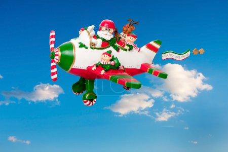Photo pour Père Noël pilotant son avion avec la bannière Happy Holidays dans le ciel avec ses elfes et Rudolf le renne au nez rouge . - image libre de droit