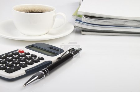 Desk with a calculator, journals, pen and coffee f...