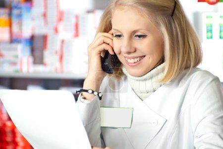 Photo pour Pharmacien lecture sur ordonnance à la pharmacie et de parler au téléphone - image libre de droit