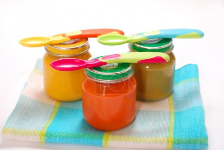 Foto de Frascos de diversos alimentos para bebés y cucharas aisladas en blanco - Imagen libre de derechos