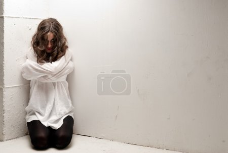 Photo for Young insane woman with straitjacket on knees looking at camera - Royalty Free Image