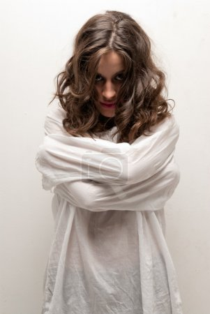 Photo for Young insane woman with straitjacket standing looking at camera - Royalty Free Image