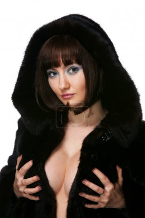 The sexy girl in a fur coat on a white background
