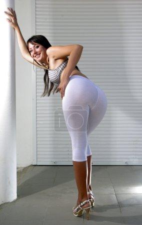 Happy brunette bending on a white street in white leggings