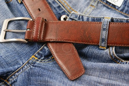 Blue jeans and a brown leather belt.