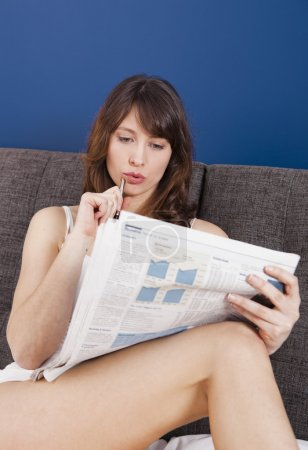 Photo for Beautiful young woman lying on the bed and seek for a job on the newspaper - Royalty Free Image