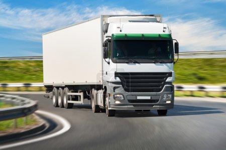 Photo pour Camion blanc sur la route, flou de mouvement. - image libre de droit