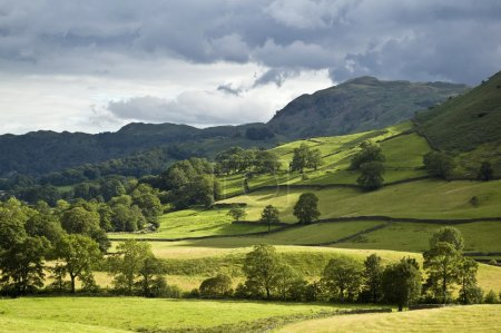 Photo for Country scene of green lush hills with dramatic sky - Royalty Free Image