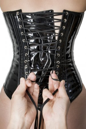 Male hands tightening up a corset