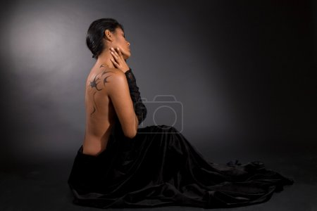 Photo for Beautiful woman sitting on black background surrounded by black velvet - Royalty Free Image